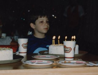 Preparing to blow out the candles for my birthday cake at Showbiz Pizza in 1987