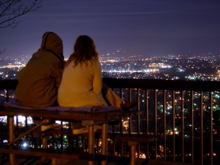 A couple sits on a picnic table, looking out over the city of Roanoke.