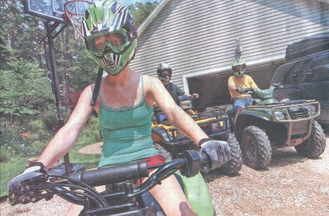 Lauren Sohn rides the ATV while wearing short shorts and a tank top