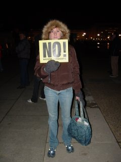 """This woman held a sign that said """"NO MORE TROOPS""""."""
