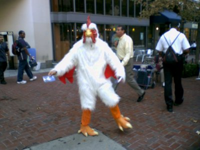 A man in a rooster costume hands out literature at Dupont Circle station