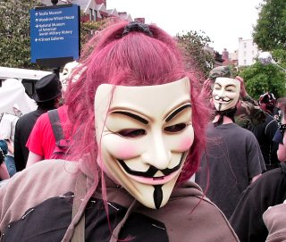 A woman wearing a Guy Fawkes mask