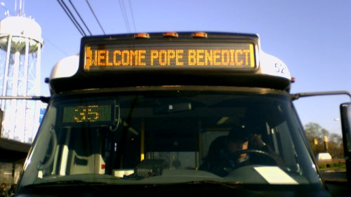 "Ride On cutaway displaying ""Welcome Pope Benedict"" on its sign"