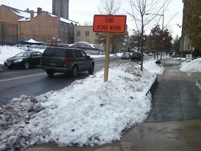 Snow piled around a road construction sign.