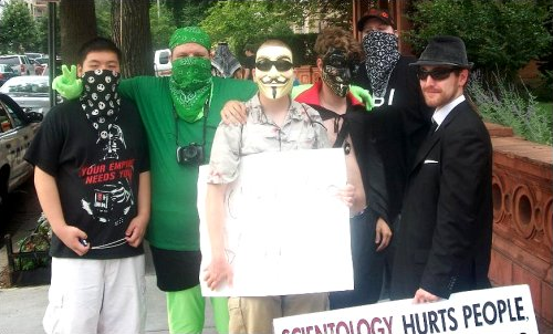 "Group photo, with a bunch of us posing in our masks outside the Org. I am shown here in my ""alternate"" mask. When I wasn't wearing the zentai hood, I simply wore a second green bandanna to maintain the ""anonymous"" look."