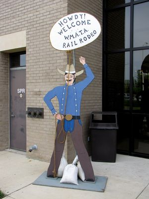 Wooden cowboy cutouts outside the shops building, welcoming people to the Rail Rodeo.