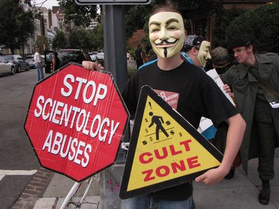 Our New York Anon holds up a sign done up to resemble a road sign.