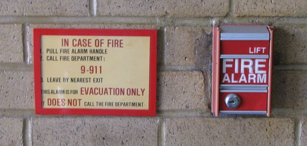 "Then this was the pull station configuration. They had ""lift"" pull stations, and a notice next to them instructing would-be heroes that the alarm does not automatically call the fire department, and that the fire department must be called separately."