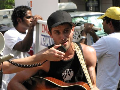 A man plays a guitar, and sings through a bullhorn.