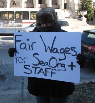 "HT raids maskless, with a ""Fair wages for Sea Org"" sign."