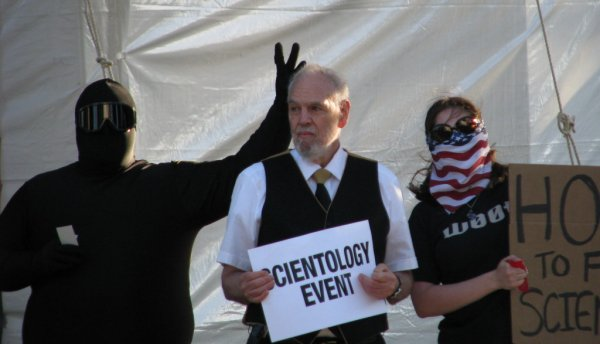 Giving rabbit ears to a Scientologist on the corner.