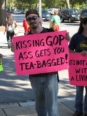 """Kissing GOP ass gets you TEA-BAGGED!"" Best. Sign. Ever. After all, the GOP is not really concerned with the Tea Party's best interests. The Tea Party will be the first ones in line to get screwed by Republican initiatives."