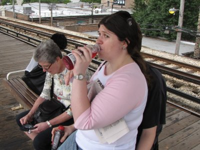 """Ann Lysy has a drink on a Chicago """"L"""" train platform"""
