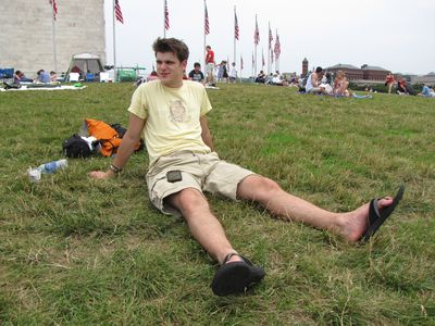Jory sits on the grass in front of the Washington Monument.