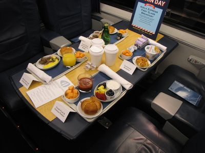This is a display of the Acela breakfast options. Starting at the bottom and going clockwise, you have the fresh fruit and cheese platter, the mushroom and swiss omelet, the French toast with fresh berry medley, and then the continental breakfast.