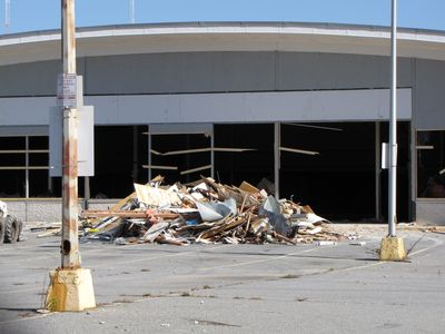 Debris piled in front of the store. Note that besides the windows' having been removed, part of the concrete portion of the wall has already been demolished. I'm guessing that this was done to allow heavy equipment into the building to demolish the interior.