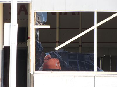 "Broken glass on one of the front windows. Notice the ""Welcome to SAFEWAY"" lettering on the back wall of the store."