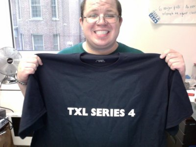 "Holding up my ""TXL SERIES 4"" shirt"