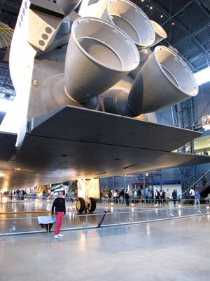 Mom stands under Enterprise's body flap, with the main engines in frame