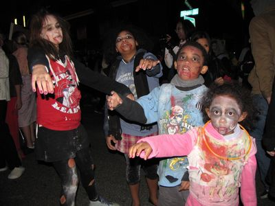 Four kids dressed as zombies. These four kids certainly knew how to ham it up for the camera, all right, however, the smallest one (wearing pink) didn't quite know how to handle photographers, in that she reached out and touched the camera.