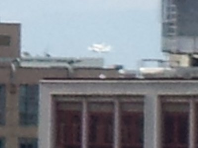 Highly zoomed in image of Discovery riding piggyback on the airplane as it buzzes the Mall (my building is in Dupont Circle, north of the Mall).