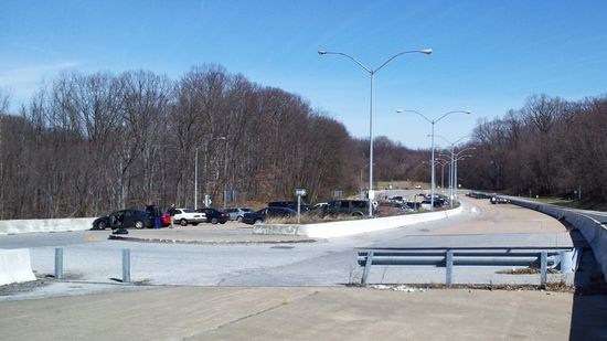 Overview of the I-70 park and ride from the western end of the facility. The intended westbound lanes (where most of the cars are parked) are to the left of the barrier in the center of the photo, while the intended eastbound lanes are to the right of said barrier.