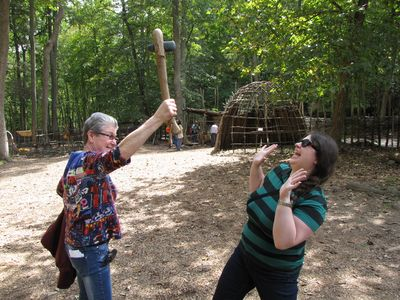 Mom holds up a handmade axe as Sis acts scared.  Despite appearances, that axe blade is actually pretty sharp!