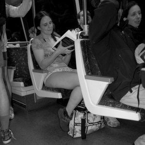 A woman reads a book while on Alstom 6027 (note the wool seat covers and gray floor).