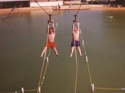 This photo shows two men going down the zip line, taken from the top of the tower.  On the cable ride, people would hang from the handholds and ride the cable to the end of the lake near the beach house.