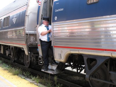 The conductor stands in the door as the train begins to leave Staunton Amtrak station.