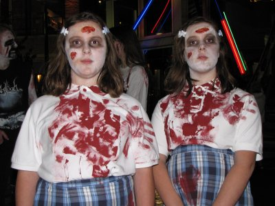 Two children dressed as zombies, looking far too wholesome to be covered in blood.  And the blank expressions add to the scary effect.