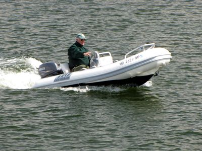 A man drives a powerboat down the harbor, seen from near the Compromise Street bridge.