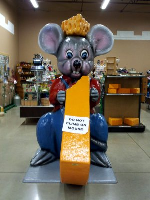 A giant mouse eating a big piece of cheese, while wearing a cheese hat.
