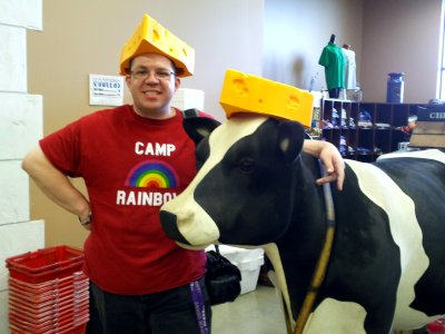 I pose with the cow, sporting a cheese hat