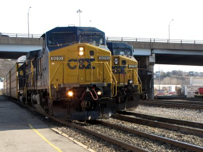 CSX locomotive 9010 passes by, pulling a full load of freight cars behind it.