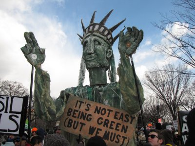 "The Statue of Liberty, with a sign saying, ""It's not easy being green (but we must)."""