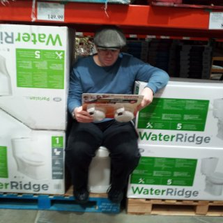 First of all, show of hands: who already knew that Costco sold toilets? That said, here I am, doing a fit test on said commode, complete with reading material.