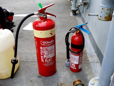 Two Chubb-brand fire extinguishers.  The larger extinguisher on the left uses foam, while the smaller extinguisher uses carbon dioxide.