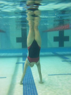 Suzie does a handstand on the bottom of the pool.