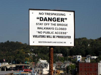 """Sign warning would-be adventurers away from the Western Maryland Scenic Railroad bridge.  The scare quotes, though, amused me.  Why the scare quotes around """"danger"""" and """"no public access""""?  Is that code for something else, like the entrance to a villain's secret lair or something?"""