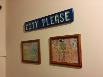 "The ""CITY PLEASE"" sign is one that I carved in an art class in 11th grade.  It was based around my job at that time as a directory assistance operator, where we used to answer calls, ""City, please?""  Yeah, I was a geek back then, too.  Then beneath it are two drawings that I did of Power Rangers settings.  One is of a Purple Ranger character that my sister came up with, done in the Mighty Morphin and Zeo costume styles.  I'm really pleased about how that Command Center (the Brandeis-Bardin House of the Book in real life) came out.  The other picture is one that I drew of Lord Zedd in his palace, with his throne behind him, and Z-Putties on either side.  I scanned both of these drawings back in 2012."