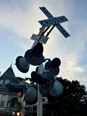 Railroad crossing signal with two sets of lights and crossbucks. The lights and crossbuck facing left are for traffic on Main Street, while the other set, facing approximately forward, is for traffic on Liberty Street.