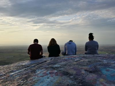 Four teens sitting on High Rock, all checking their phones.