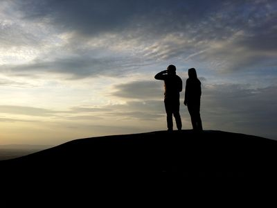 Two people stand on High Rock, looking out over the landscape. View facing west.
