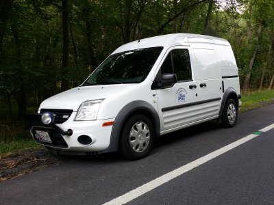 "White Ford Transit Connect van with ""Safe Speed"" on the door"