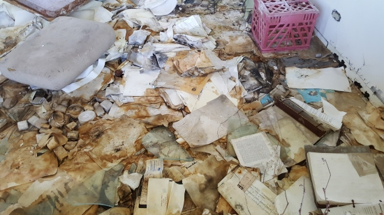 Documents scattered all over the floor, in noticeably worse condition than 2013