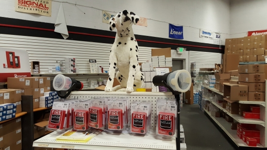 Display of Fire-Lite BG-12s, complete with large stuffed dalmatian. The dalmatian is Fire-Lite's mascot.