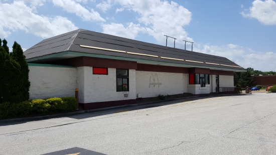 Exterior, with new roof going on, covering the double mansard that the facility had when it was still in operation. Also note the McDonald's labelscar on the side of the building. Guessing that they paint the exterior in order to hide these labelscar markings.