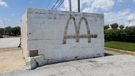 McDonald's labelscar on the dumpster enclosure. Guessing that this will be painted out as well.
