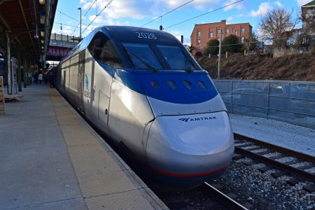 An Acela Express train services the station on its way to DC.